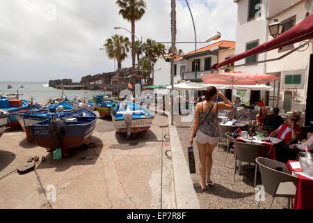 Tourists, restaurant and boats  in the harbour, Camara de Lobos, Madeira, Europe - Stock Photo