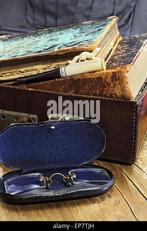 Old stuff. Leather suitcase with old books, cigarette holder with a bone carving and pince-nez in a metal box. - Stock Photo