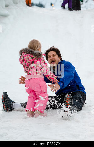 Laughing father slides down snow slide with his young daughter at Squaw Valley Ski Resort in California - Stock Photo