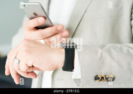 OSTFILDERN, GERMANY - MAY 14, 2015: A businessman is checking his Apple Watch while using his iPhone 6. The Apple - Stock Photo