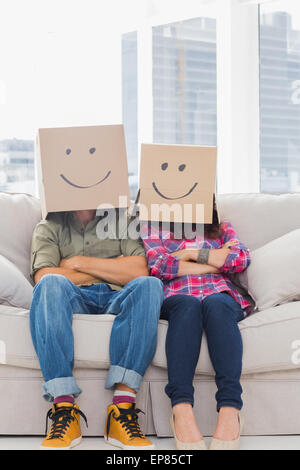 Funny workers with arms folded wearing boxes on their heads - Stock Photo
