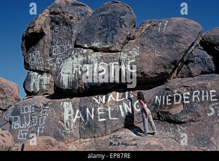 Spray-painted names and other graffiti deface the boulders and natural scenery in the desolate Mojave Desert near - Stock Photo