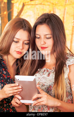 Beautiful young trendy girls using tablet - Stock Photo