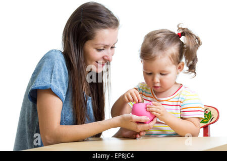Mother and daughter put coins into piggy bank - Stock Photo