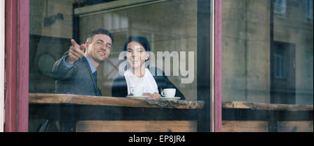 Happy businessman pointing on something in cafe - Stock Photo