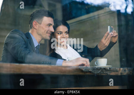 Smiling businesswoman and businessman making selfie photo on smartphone in cafe - Stock Photo