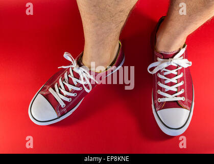 White male human legs and feet wearing a pair of red canvas trainers with background - Stock Photo