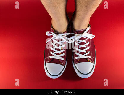 Male human legs and feet wearing a pair of red canvas trainers with background - Stock Photo