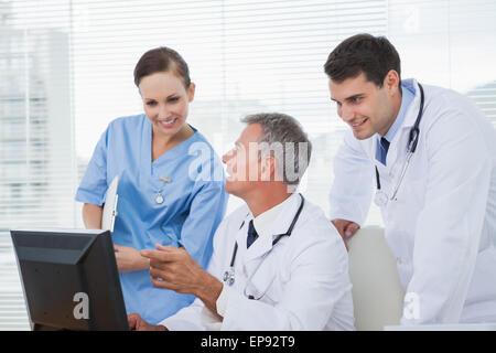 Cheerful doctors and surgeon working together on computer - Stock Photo