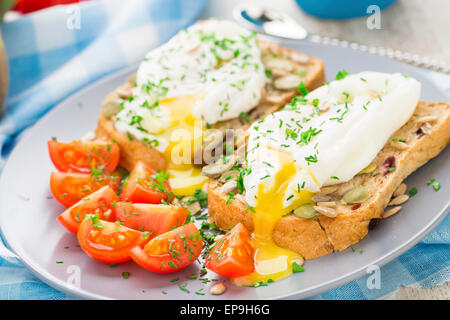 Breakfast sandwich with poached egg and cherry tomatoes. - Stock Photo