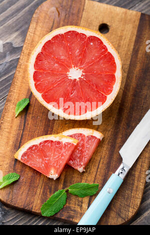 Grapefruit with slices on a wooden table. - Stock Photo