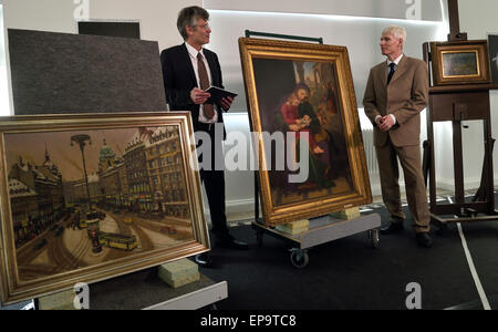 Chemnitz, Germany. 15th May, 2015. Head of the Deutsches Zentrum Kulturgutverluste (German Lost-Art Foundation) Uwe Hartmann (l) and art historian and provenance researcher Kai Artinger stand alongside three paintings of various provenience, at the Kunstsammlungen Chemnitz, Germany, 15 May 2015. There are indications that six artworks at the Kunstsammlungen Chemnitz were unlawfully taken from their original owners during the Nazi period. This includes the picture 'Mutter Anna lehrt Maria lesen' (lit. Mother Anna teaches Maria to read) (M) by Carl Christian Vogel von Vogelstein. PHOTO: HENDRIK