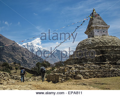 Two Nepalis walk past a stupa on a pass between Khumjung and Namche Bazaar in the Himalayas of Nepal - Stock Photo