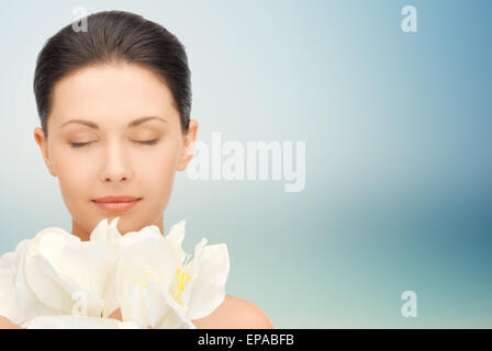 beautiful woman smelling flowers with closed eyes - Stock Photo