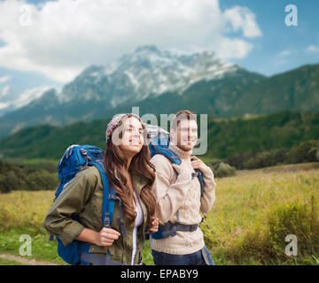 smiling couple with backpacks hiking - Stock Photo