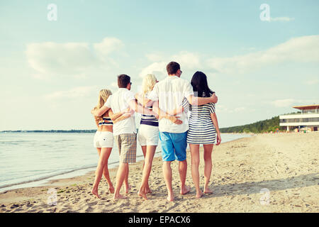 smiling friends hugging and walking on beach - Stock Photo