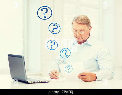 old man in eyeglasses filling a form at home - Stock Photo