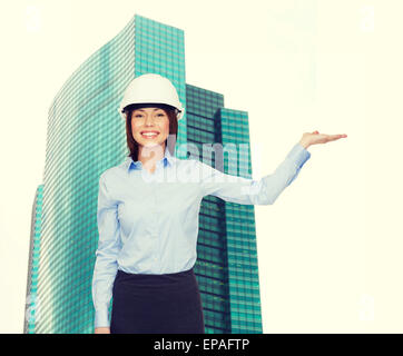 businesswoman in helmet holding something on palm - Stock Photo