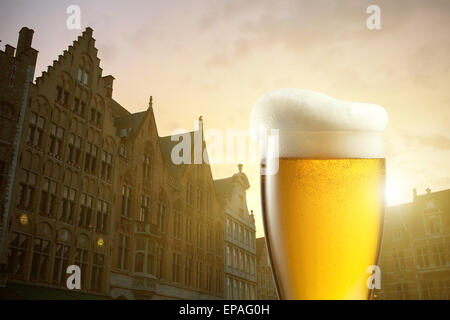 Glass of beer against silhouettes of houses in Bruges, Belgium - Stock Photo