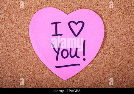 An I Love You message written on a piece of heart-shaped note paper. - Stock Photo