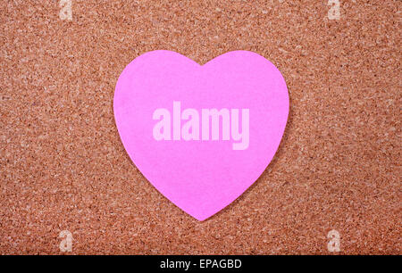 Memo paper in the shape of a Heart stuck on a noticeboard. - Stock Photo
