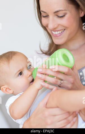Mother feeding baby with milk bottle - Stock Photo