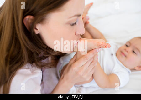 Mother kissing her babys leg on bed - Stock Photo