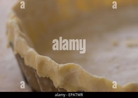 Pastry rolled out and lining a fluted flan dish, ready to cook - Stock Photo