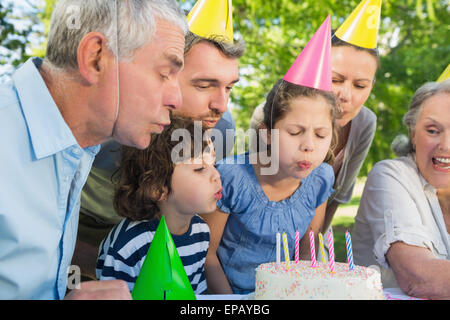 Extended family in party hats blowing birthday cake - Stock Photo