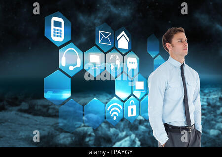 Composite image of serious businessman standing with hands in pockets - Stock Photo