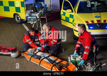 Paramedics helping motorbike driver on stretcher - Stock Photo