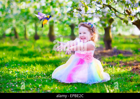 Child playing with a bird. Happy laughing little girl in fairy costume with wings feeding a pet parrot in a cherry - Stock Photo
