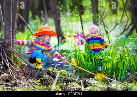 Children playing outdoors. Preschool kids catching frog with net. Boy and girl fishing in forest river. - Stock Photo