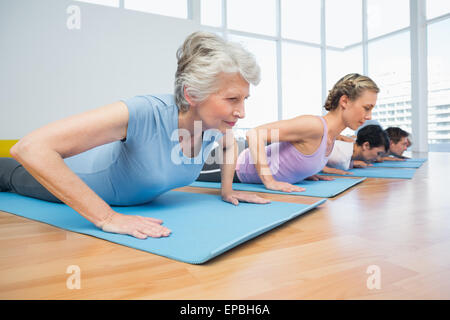 Group doing cobra pose in row at yoga class - Stock Photo