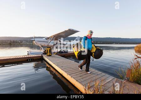 Visitor unloading gear from a flotaplane, Homer, Kenai Peninsula, Southcentral Alaska - Stock Photo