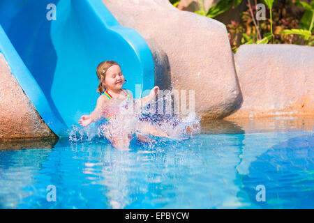 Happy little girl on water slide in a swimming pool having fun during summer vacation in a beautiful tropical resort - Stock Photo
