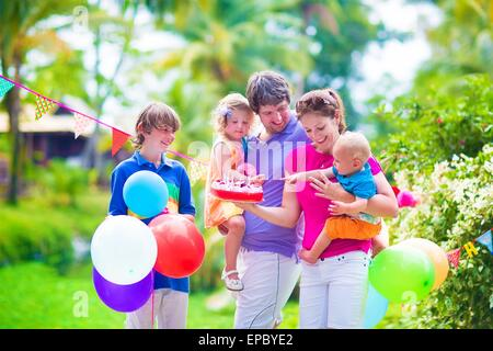 Happy big family with three children, teenager boy, cute curly toddler girl and a little funny baby celebrating - Stock Photo