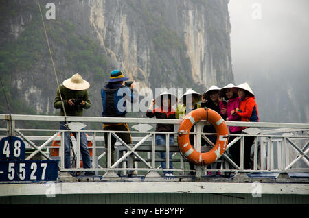 Five women wearing coolie hats line up for photo on top of passenger boat, and man looks at his camera; Halong Bay, - Stock Photo