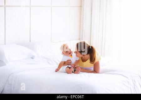 Young happy mother holding her adorable baby, cute blond curly boy, playing in a white bed enjoying a sunny morning - Stock Photo