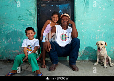 Camilo Saenz gathers with his children in his porch after a hard day of work. - Stock Photo