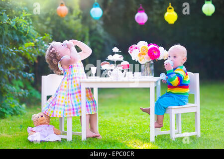 Two happy children, cute curly toddler girl and a little baby boy, brother and sister, enjoying a tea party with - Stock Photo