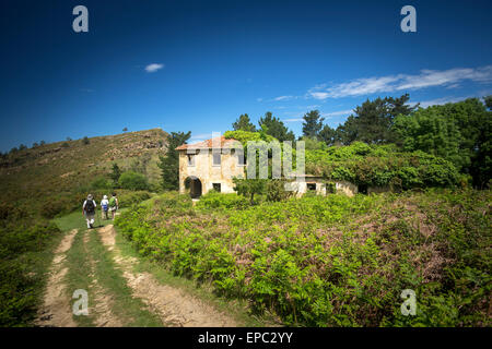 Hikers passing in front of an ivy-covered abandoned  house (Guipúzcoa - Spain). Randonneurs passant devant une maison - Stock Photo
