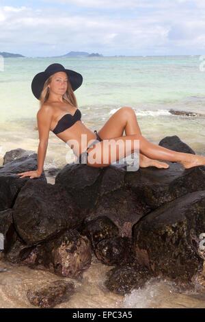 beautiful blond in a black hat and bikini on the rocks in Hawaii - Stock Photo