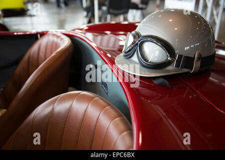 helmet and glasses resting on a luxury convertible sports car - Stock Photo