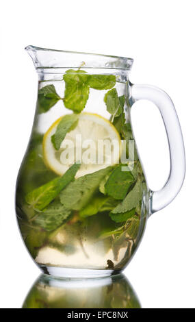 Alcoholic cocktail with mint and lemon slice in a pitcher. Full jug of mojito. - Stock Photo