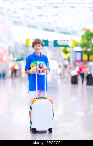 Happy excited teenager boy travelling alone by airplane, standing at Dusseldorf international airport terminal with - Stock Photo