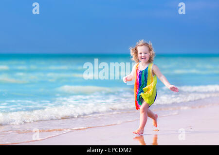 Happy laughing little girl in colorful rainbow bathing suit running and playing on ocean coast on tropical island - Stock Photo
