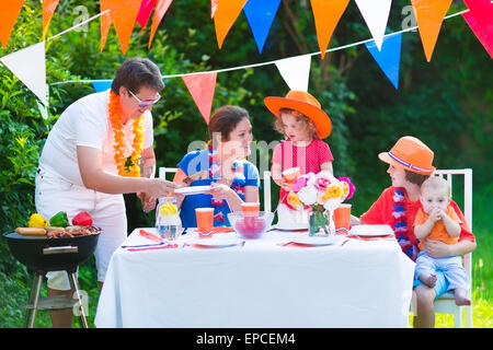 Happy big Dutch family with kids celebrating a national holiday or sport victory having fun at a grill party in - Stock Photo