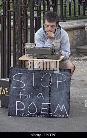 An poet and street busker soliciting money for writing poems in Union Square Park, New York City - Stock Photo