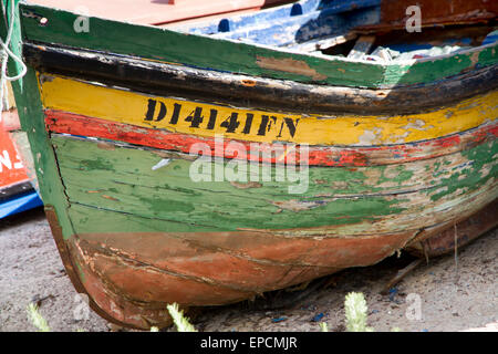 Flaking paint on abandoned wooden boat in Camara de Lobos harbour on Madeira - Stock Photo